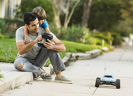 lifestyle image of father and son playing with a RC car